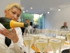 BERLIN, GERMANY - JULY 02: A waitress poors champagne at the Samsung Designer Soiree at Epicentro art gallery during the Mercedes-Benz fashion week spring and summer 2014 on July 2, 2013 in Berlin, Germany. (Photo by Alexander Becher/Getty Images for Samsung)